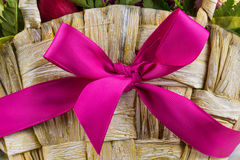 A wooden basket with pink ribbon. And flowers Stock Photography