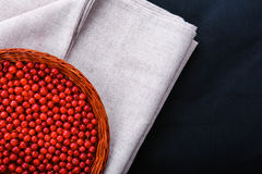 A wooden basket with red currant on a dark blue background. Fresh and ripe red currant. Berries on a gray fabric. Organic foods. Royalty Free Stock Photo