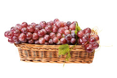 Wooden basket and ripe grapes on a white. Stock Image