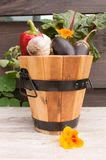 Wooden basket with vegetables on a wooden background royalty free stock photography