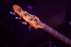 Wooden bass guitar fretboard in purple concert light. A wooden bass guitar fretboard in the purple concert light royalty free stock photo