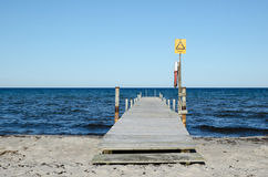 Wooden bath pier with sign for shallow water Stock Images