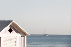 A wooden bathing box and a sailing boat Royalty Free Stock Images