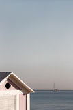 A wooden bathing box and a sailing boat Stock Photography