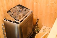 Wooden bathroom with a heating pot filled with stones Wooden sauna interior with equipment. Rest and relaxation in the. Wooden bathroom with a heating pot filled royalty free stock photography