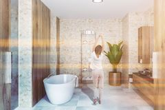 Wooden bathroom interior, black sink, tub, woman. Young woman in luxury bathroom with wooden walls, white tile floor, black double sink standing on wooden and royalty free stock photo