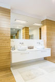 Wooden bathroom with mirror and sinks. Large spacious bathroom finished in wood with large mirror and two white sinks royalty free stock image