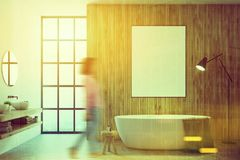 Wooden bathroom, poster toned. Wooden bathroom interior with a loft window and a white tub with a poster hanging above it. A double sink with round mirrors. A royalty free stock photos