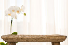 Wooden bathroom table on abstract blurred background with orchid flower royalty free stock photography