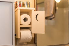 Wooden bathroom toilet paper dispenser and holder with crescent moon door.  Even in the bathroom, paperwork is never done. Royalty Free Stock Photos