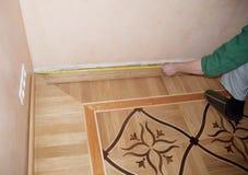 Wooden batten installation and repair on oak wood parquet. Contractor hands measuring wooden batten with measure tap stock photography