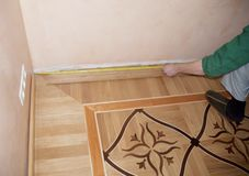 Wooden batten installation and repair on oak wood parquet. Contractor hands measuring wooden batten with measuring royalty free stock image