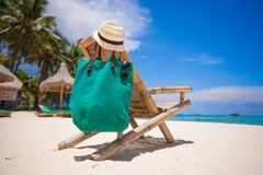 Wooden beach chair with hat and bag on white sand Stock Photo