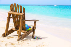 Wooden beach chair with hat and slippers and sunglasses at tropi Stock Images