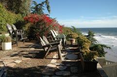 Wooden Beach Chairs overlooking Ocean Stock Photo