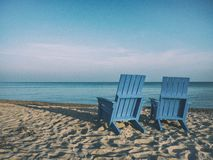 Wooden beach chairs on sandy beach