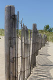 Wooden Beach Fence on Sand Dunes with Blue Sky Stock Photo