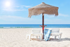 Wooden beach umbrella and sun bed on the beach. Royalty Free Stock Photo