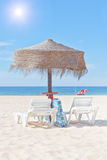 Wooden beach umbrella and sun bed on the beach. Royalty Free Stock Images