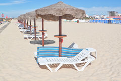 Wooden beach umbrellas in a row on a sunny beach. Royalty Free Stock Photo