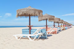 Wooden beach umbrellas and sunbeds on the beach. Royalty Free Stock Image