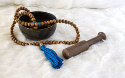 Wooden beads with blue tassel on white fur Royalty Free Stock Image