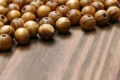 Wooden beads close-up on a background of wooden boards. Stock Photo