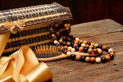 Wooden beads, wooden casket and hairbrush on table Stock Photography