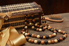 Wooden beads, wooden casket and hairbrush on table Stock Image