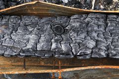 Wooden beam with screws after the fire. Charred beams in rusty gutter Royalty Free Stock Photo