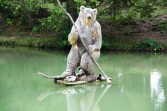 Wooden bear and resting ducks on the lake. Beautiful piece of art, wooden bear with a paddle and wooden skies on the lake with resting ducks by his legs stock photos