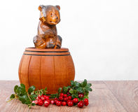 Wooden bear on small barrel with bunch of lingonberries Stock Image