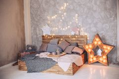 Wooden bed in the bedroom with beautiful decorative elements and a glowing garland. Wooden bed in the bedroom with beautiful decorative elements Stock Photos