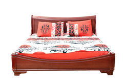 Wooden bed with colorful linen Royalty Free Stock Image