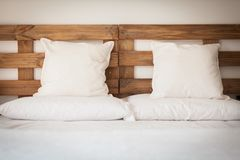 Wooden bed with white linen Stock Images