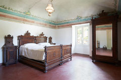 Wooden bedroom in ancient interior with fresco Stock Photos