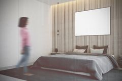 Wooden bedroom, poster side blur. Wooden bedroom interior with a carpet on the floor, a gray bedcover on a master bed, two bedside tables and a poster. Side view Royalty Free Stock Photography