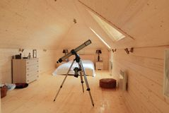 Wooden bedroom with telescope stock photos