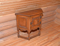 The wooden bedside table stands near a timbered wall Stock Image