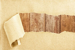 Wooden behind torn paper. Wooden texture behind torn recycled paper Stock Photo