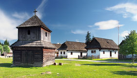Wooden bell tower and folk houses. Rare wooden bell tower with folk houses in background. These preserved constructions are located in open-air museum of Liptov Royalty Free Stock Photo