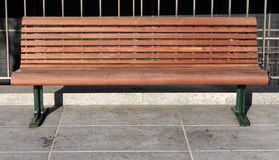 Wooden Bench. A wooden bench on a concrete ground in the sun, in front of a metal grated fence Stock Images