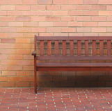 A wooden bench. Against brick wall stock image