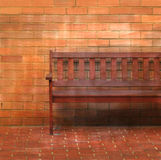 Wooden bench. A wooden bench against a brick wall stock photography