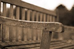 Wooden Bench. Lonely wooden bench in the park. Only part is in focus, the rest is intentionally blurred Stock Photos