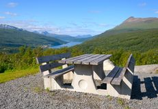 Wooden bench against the Norwegian fjord. Wide-angle photo Royalty Free Stock Image
