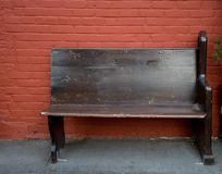 Wooden bench against red brick wall. On the street Stock Photography