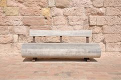 Wooden bench against a stone wall Stock Image