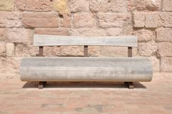 Wooden bench against a stone wall Stock Images