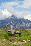 Wooden bench and in the background the Austrian Alps Stock Image